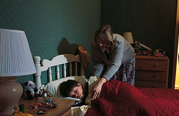 getty_rf_photo_of_mother_tucking_son_into_pleasant_bed
